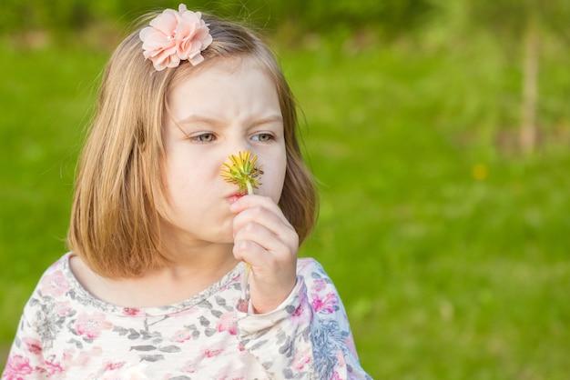 Красивая белокурая маленькая девочка нюхает желтый одуванчик и получает дозу сезонной аллергии