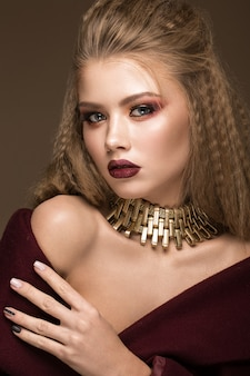 Beautiful blond model with bright makeup, gold jewelry and red lips.