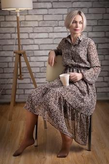Красивая белокурая задумчивая зрелая женщина, держащая чашку чая или кофе, сидя на стуле у себя дома, думая.