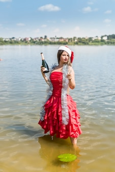 シャンパンと水中でポーズをとる美しいブロンド