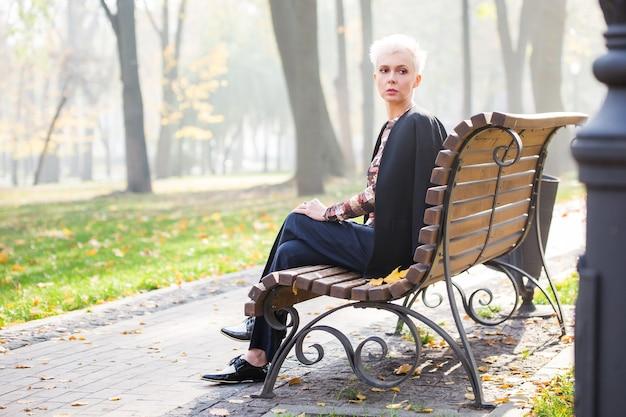 Красивая блондинка стильная женщина в осеннем парке на скамейке