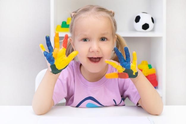 彼女の手にカラフルな塗装、幸せそうに笑って美しい金髪の幼児の女の子