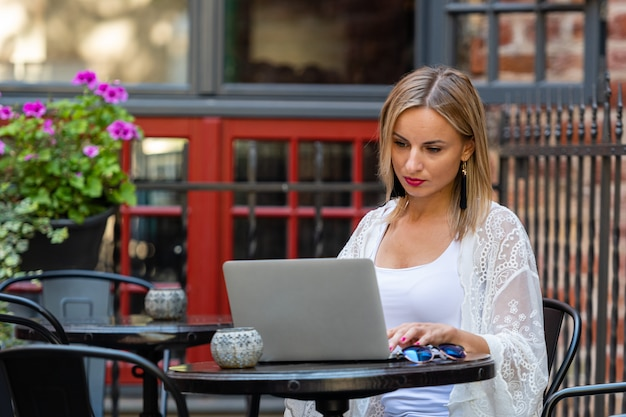 Beautiful blond woman dressed in  light clothes sitting in outdoor cafe and working with computer