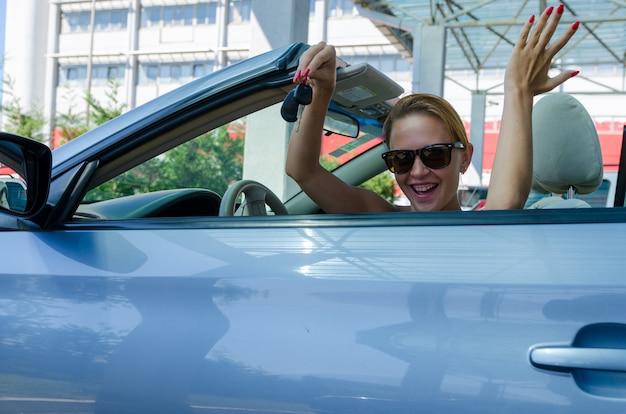彼女のコンバーチブル車を運転して美しい金髪の女性