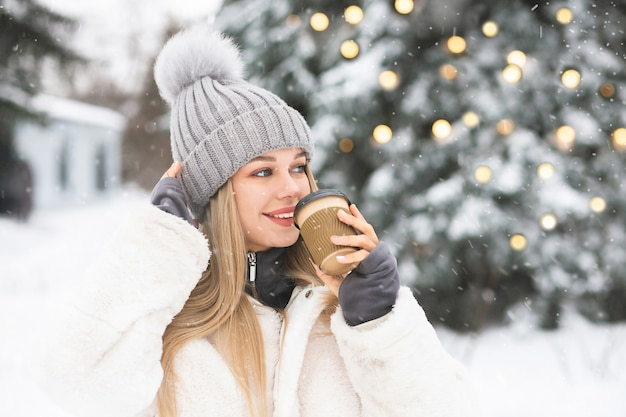 降雪時にコーヒーを楽しんでいる美しいブロンドの女性。空きスペース