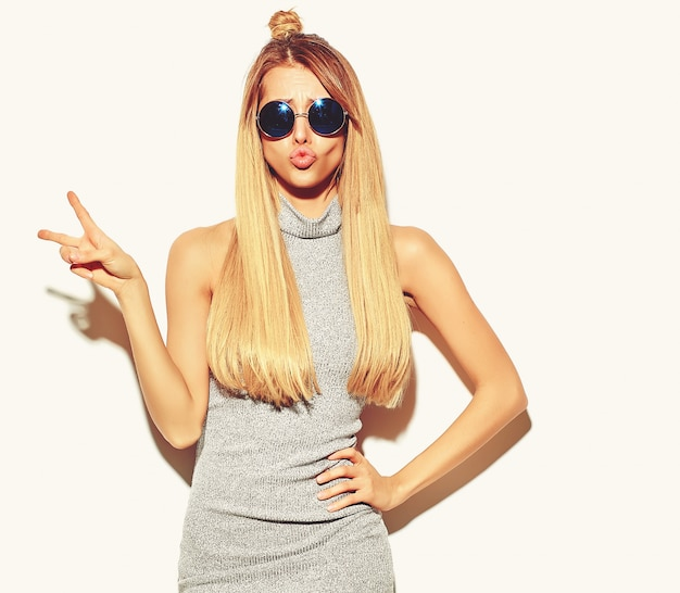 Beautiful blond woman girl in casual hipster gray summer clothes with no makeup isolated on white making a duck face and showing peace sign and making a duck face