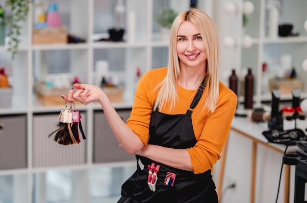 笑顔と染毛のためのカラフルなサンプルを保持している美しいブロンドの女性美容師