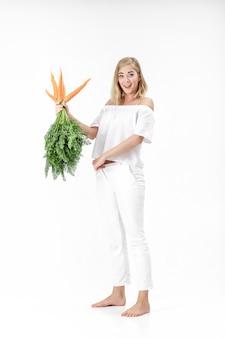 흰색 바탕에 녹색 잎 신선한 당근을 들고 아름 다운 금발 여자. 소녀는 당근을 먹고 얇게 자랍니다.