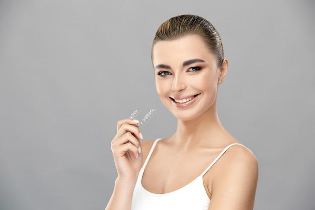 Красивая блондинка женщина держит в руке невидимые брекеты и улыбается, концепция стоматологии, здоровая и идеальная улыбка