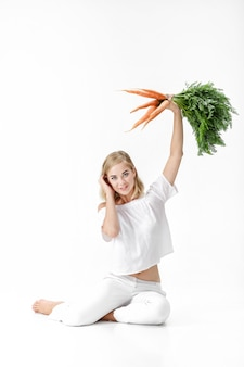 흰색 바탕에 녹색 잎 신선한 당근을 들고 흰 블라우스에 아름 다운 금발 여자. 건강과 다이어트