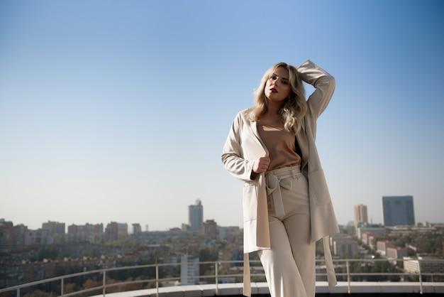 家の屋上に立っているベージュのコートを着た美しい金髪の女性。