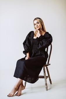 블랙 리넨 드레스에 아름 다운 금발 여자입니다. 에스닉 패션, 천연 직물. 소프트 선택적 초점.