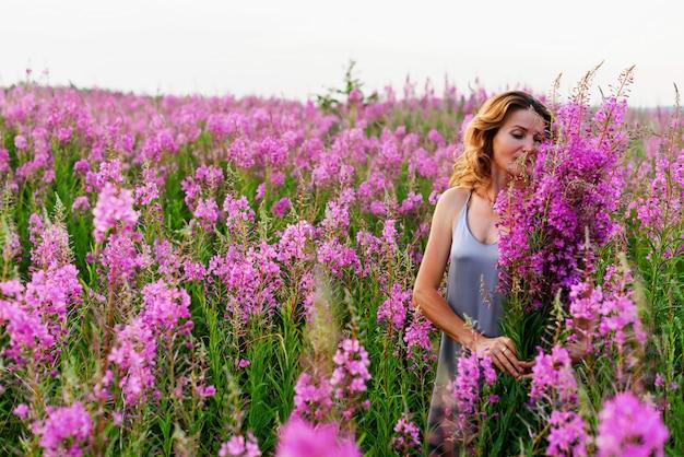 Fireweed牧草地の花の束でリラックスした灰色のドレスを着た美しい金髪の女性
