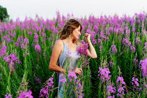 Fireweed牧草地の花の束とリラックスできる灰色のドレスを着た美しい金髪の女性