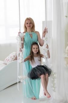 딸과 함께 해군 그리스 드레스에 아름 다운 금발 여자