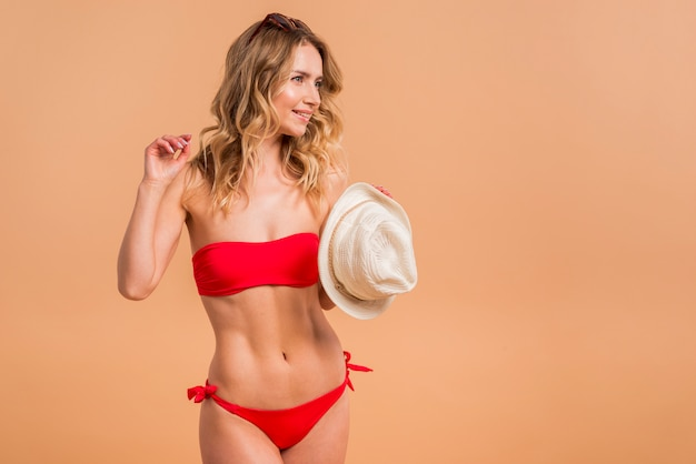 帽子を保持している赤い水着で美しい金髪の女性
