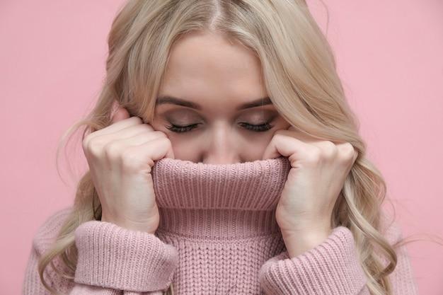 柔らかいピンクの暖かいセーターで美しい金髪の女性は目を閉じた。