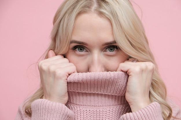 顔を覆っている柔らかいピンクの暖かいセーターで美しい金髪の女性。