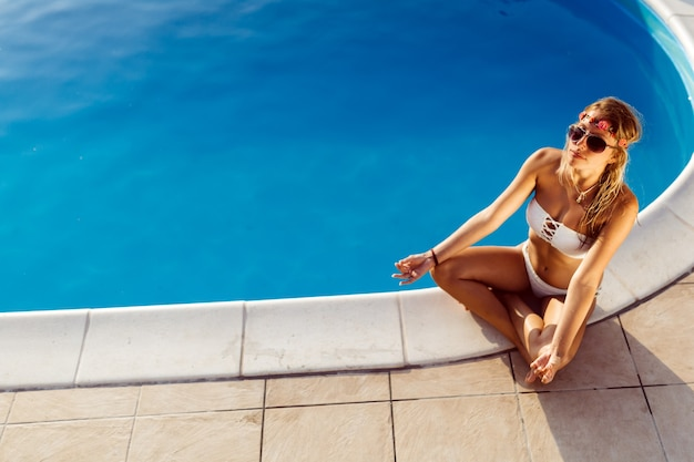 Beautiful blond woman meditating at pool