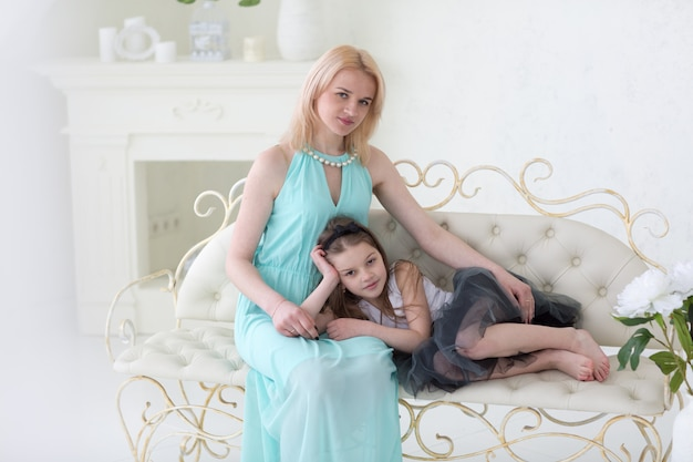 Beautiful blond woman in navy greek dress with daughter