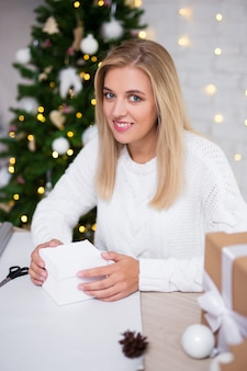 Красивая белокурая женщина, упаковывающая рождественские подарки в украшенной гостиной