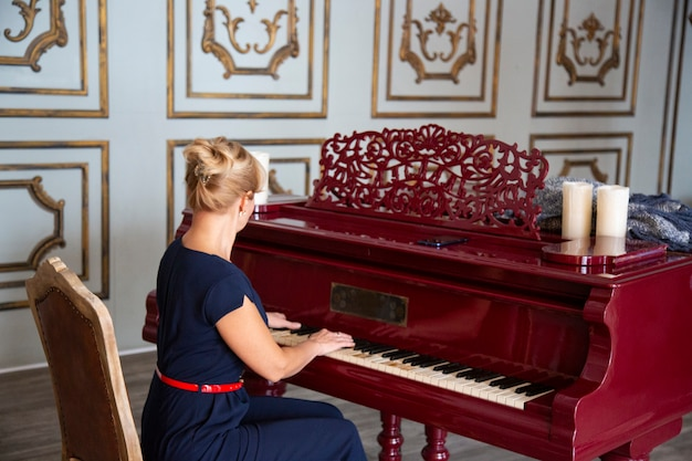 Beautiful blond woman playing on an old piano in the luxurious interior of the concert activity of creative mus