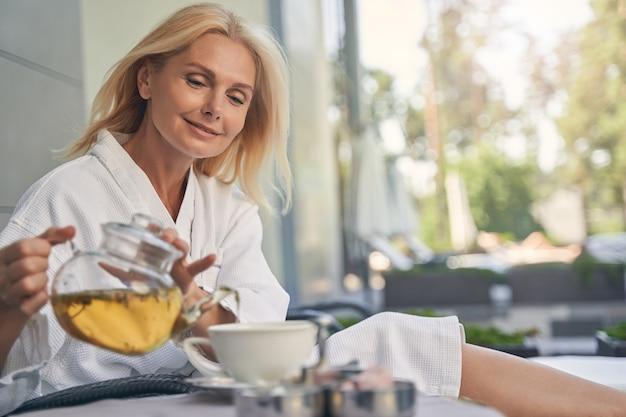 야외에서 휴식하는 동안 흰색 컵에 아름 다운 금발 여자 포링 차