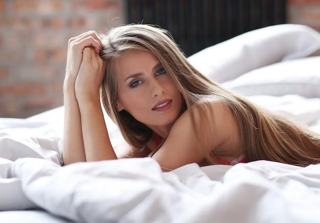 아름 다운 금발 여자 침대에 빨간 속옷에 포즈