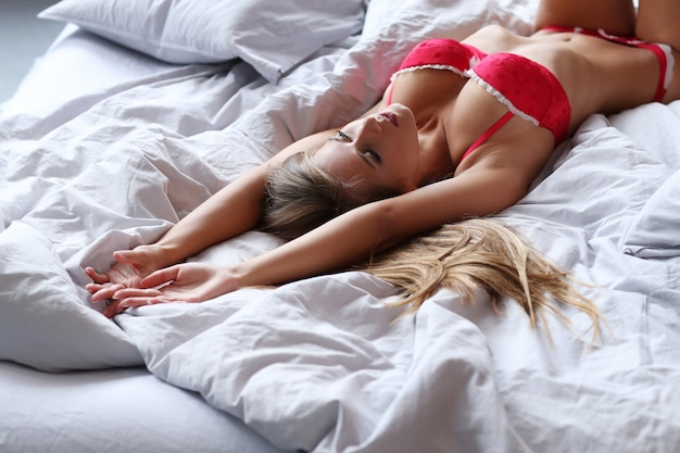Beautiful blond woman posing in red underwear on bed