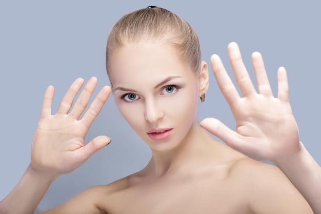 Красивая белокурая женщина защищает лицо руками на сером фоне. жест стоп крупным планом