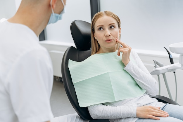 Beautiful, blond woman tells a dentist who has a toothache. woman touches cheeks