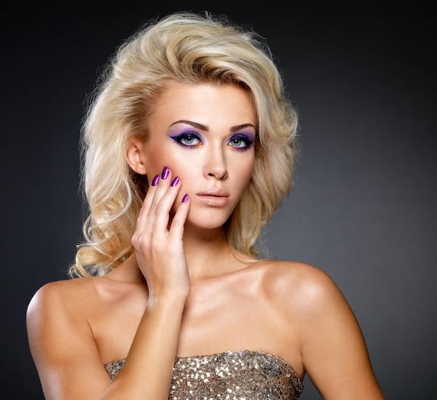 美しさの紫色のマニキュアと目のメイクで美しいブロンドの女性。巻き毛のファッションモデル。