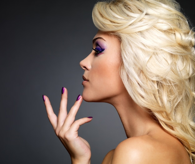 Bella donna bionda con bellezza viola manicure e trucco degli occhi. modello di moda con acconciatura riccia.