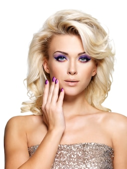 Beautiful blond woman with beauty purple manicure and makeup of eyes.