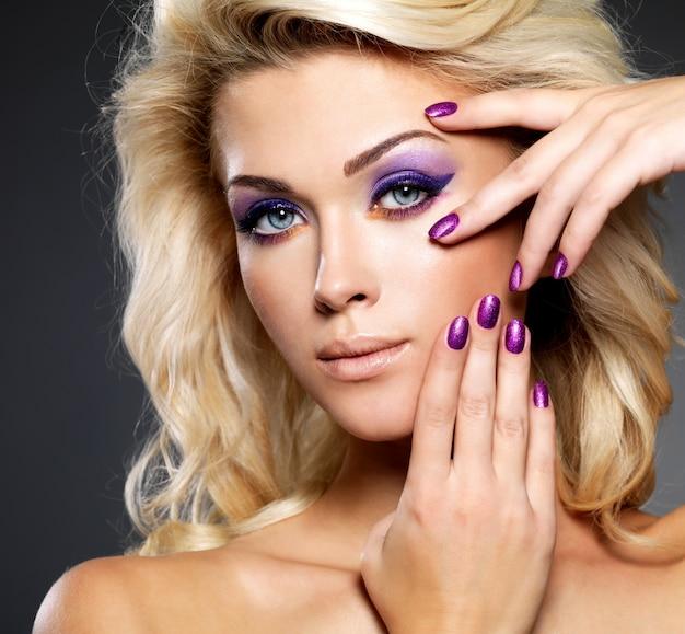 Bella donna bionda con bellezza viola manicure e trucco degli occhi