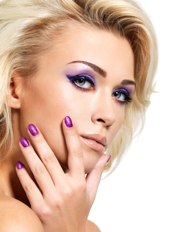 Beautiful blond woman with beauty purple manicure and makeup of eyes