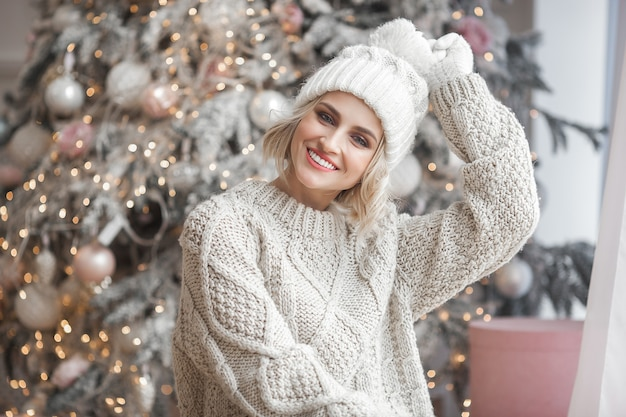 Красивая белокурая женщина с рождественской елкой. закройте вверх по портрету привлекательной девушки.