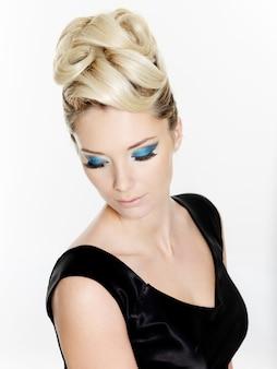 Bella donna bionda con l'acconciatura riccia e il trucco blu degli occhi isolati su bianco