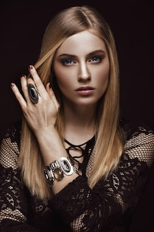 Beautiful blond woman with healthy skin and hair, red manicure, posing in studio