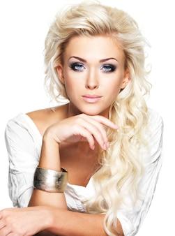 長い巻き毛とスタイルのメイクで美しいブロンドの女性。白いスペースでポーズをとる女の子