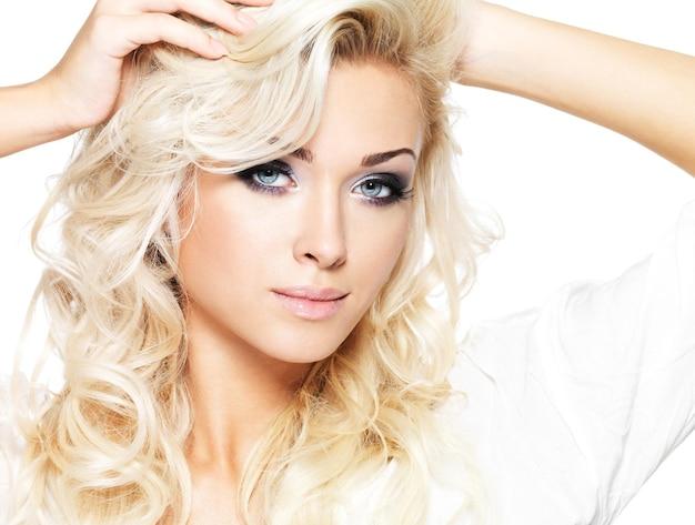 긴 곱슬 머리와 스타일 메이크업으로 아름 다운 금발 여자. 흰 벽에 포즈를 취하는 여자