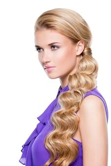 Красивая блондинка женщина с длинными вьющимися волосами, глядя в сторону - изолированные на белом.