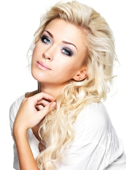 Beautiful blond woman with long curly hair and style makeup. girl posing on white space