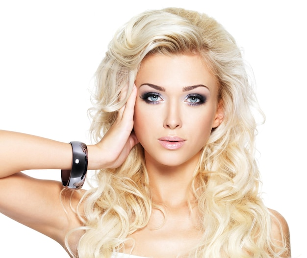 Beautiful blond woman with long curly hair and style makeup. girl posing on white wall