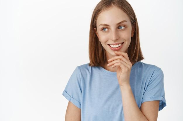 Bella donna bionda con pelle pulita naturale senza trucco e brufoli, denti bianchi sorridenti, guardando da parte il testo promozionale con espressione facciale soddisfatta, muro bianco.