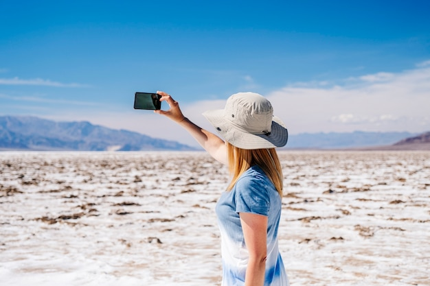 A beautiful blond woman with sun hat and yellow and white blue summer dress, takes a selfie photo with the mobile phone in the desert of death valley on a sunny day