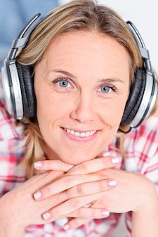 Beautiful blond womanlistening music with headphones