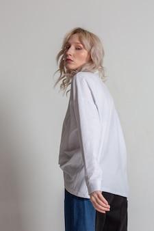 白いスタジオの背景に白いシャツでポーズをとって美しい金髪の若い女性