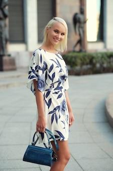 ドレスを着て通りを歩いている美しい金髪の若い女性