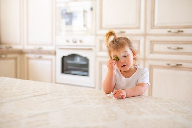Beautiful blonde baby girl having breakfast in kitchen. funny faces